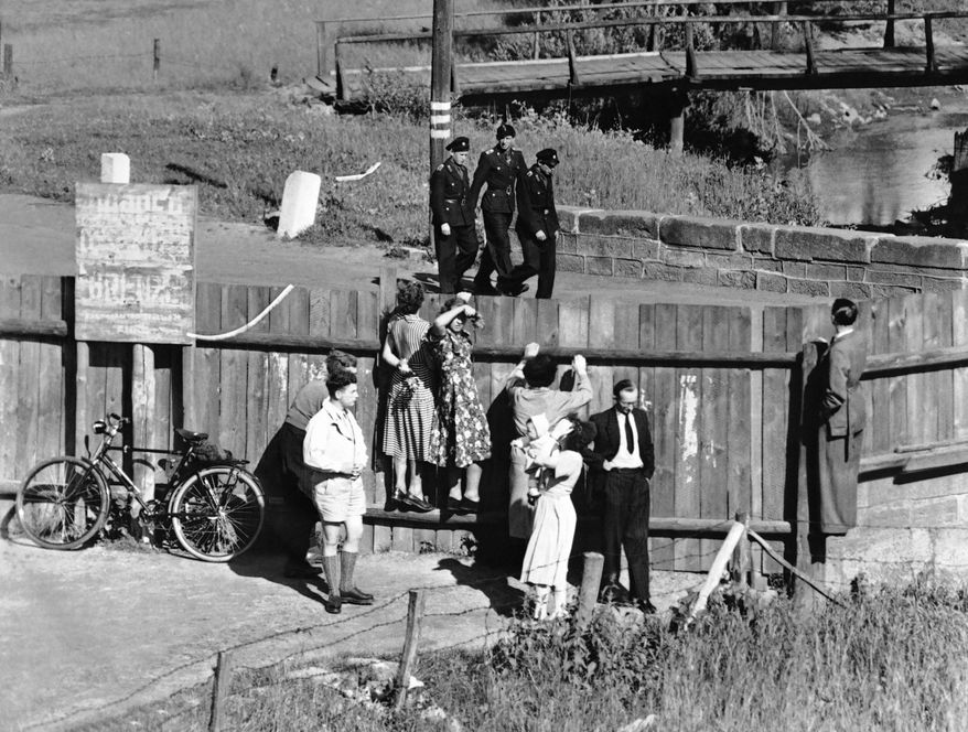 West Germans look over the fence between West and East Germany, near Vacha  on Jan. 2, 1958, at three members of the East German Communist People's Police. A visitor found the zonal border much harder to cross than it was 10 years ago. Millions of Germans cross in both directions legally every year, often to visit friends and relatives on the other side. (AP Photo)