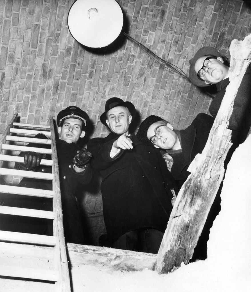 BERLIN, FEB. 3, 1962 (AP) - Communist authorities on Feb 1. 1962 showed tunnel under Wollankstrasse elevated Railway  Station they said had been driven from West Berlin to bring western Agents into red-ruled East Sector. West police contend the Tunnel was built to help refugees escape. It collapsed before it was completed. AP-Photo shows: Policeman of communist East German Railrods show reporters where Tunnel makers broke through walls under the station before starting to dig.