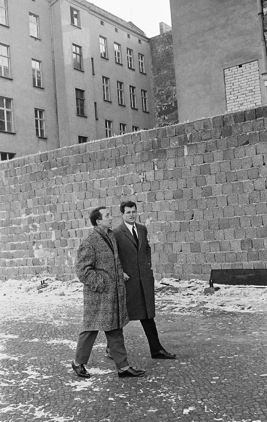 Edward Kennedy, right, in Berlin inspect the Wall at Bernauer Street on Feb. 23, 1962, accompanied by unidentified interpreter. (AP Photo/Reichert)