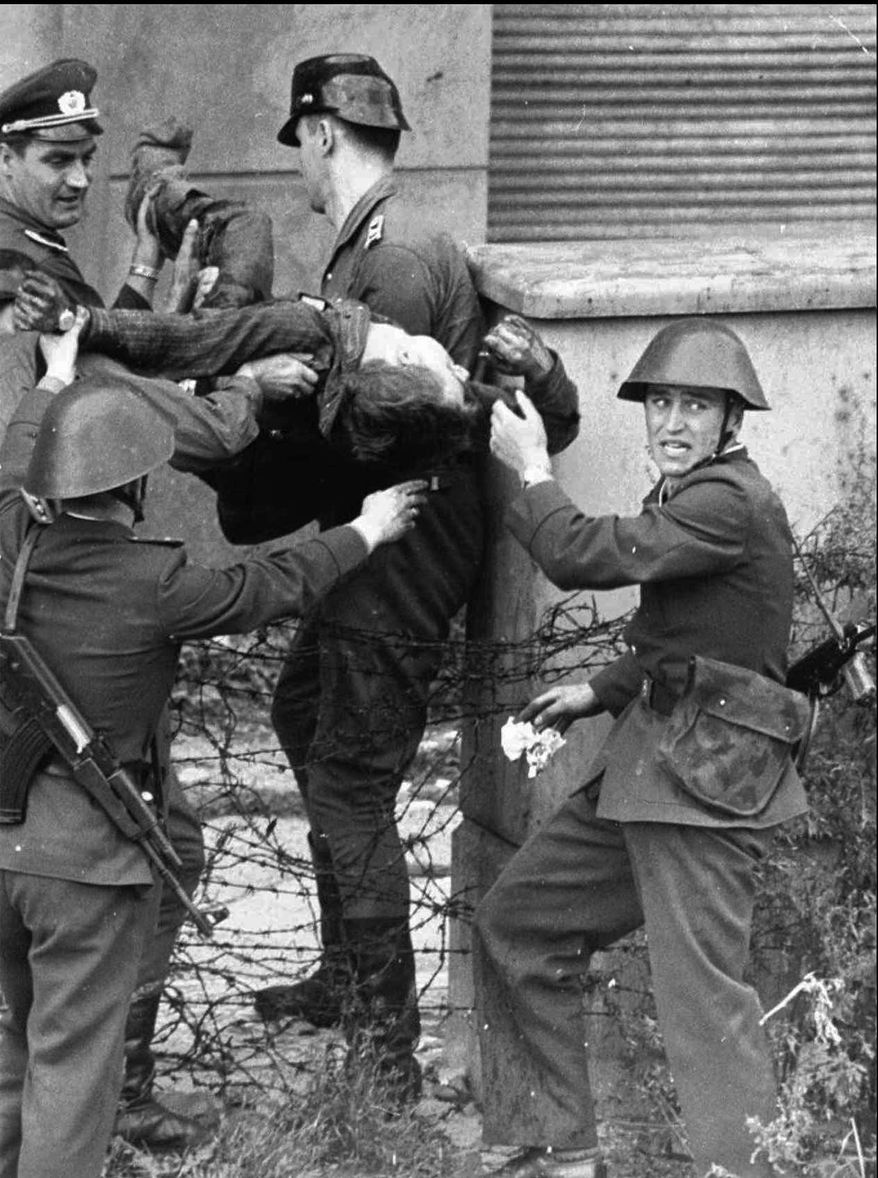 Dying Peter Fechter is carried away by East German border guards who shot him down when he tried to flee to the west  in this Aug. 17, 1962 photo.  Fechter was lying 50 minutes in no-man's land before he was taken to a hospital where he died shortly after arrival. Monday, Aug. 13, 2007 marks the 46th anniversary of the construction of Berlin Wall. The agency that manages the records of former East Germany's dreaded secret police has uncovered an order for border guards to fire on escaping citizens that is far more explicit than others on record, an official said in remarks published Saturday, Aug. 11, 2007. (AP Photo)