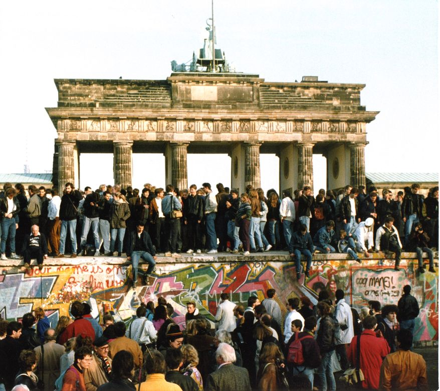 People walking on the Berlin wall in front of the Brandenburg gate after opening one day before, Nov. 10, 1989. (AP Photo)