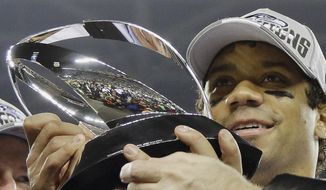 Seattle Seahawks' Russell Wilson holds up the George Halas Trophy after the NFL football NFC Championship game against the San Francisco 49ers, Sunday, Jan. 19, 2014, in Seattle. The Seahawks won 23-17 to advance to Super Bowl XLVIII. (AP Photo/Matt Slocum)