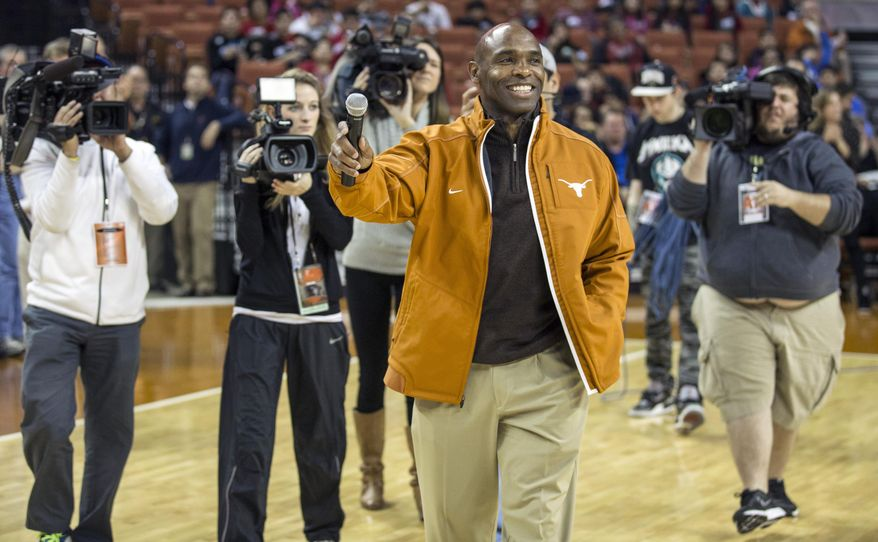FILE - In this Wednesday, Jan. 8, 2014 file photo, Texas new head football coach Charlie Strong speaks to fans during a timeout against Oklahoma in the first half of an NCAA college basketball game in Austin, Texas. There are 125 colleges playing in the top-level Football Bowl Subdivision. In 2013, 13 of them had black coaches. That was down from 15 in 2012 and an all-time high of 17 in 2011. Strong and James Franklin at Penn State have not been replaced by African-Americans, so the overall numbers remain low. (AP Photo/Austin American- Statesman, Ricardo B. Brazziell) MANDATORY CREDIT: AUSTIN AMERICAN- STATESMAN, RICARDO B. BRAZZIELL