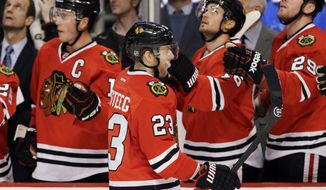 Chicago Blackhawks' Kris Versteeg (23) is congratulated by teammates after his goal during the first period of an NHL hockey game against the Anaheim Ducks in Chicago, Friday, Jan. 17, 2014. (AP Photo/Nam Y. Huh)