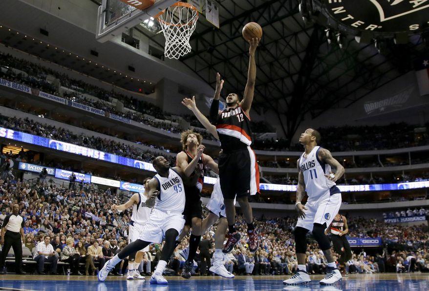 Portland Trail Blazers power forward LaMarcus Aldridge, center, goes up for a shot as Dallas Mavericks' DeJuan Blair (45) and Monta Ellis (11) defend during the first half of an NBA basketball game, Saturday, Jan. 18, 2014, in Dallas. (AP Photo/Tony Gutierrez)