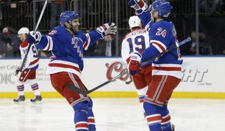 New York Rangers center Dominic Moore, left, celebrates with New York Rangers right wing Ryan Callahan (24) after Callahan scored a goal on Washington Capitals goalie Braden Holtby (not shown) in the second period of their NHL hockey game at Madison Square Garden in New York, Sunday, Jan. 19, 2014. (AP Photo/Kathy Willens)