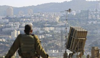 ** FILE ** In this Aug. 28, 2013, file photo, an Israeli soldier is seen next to an Iron Dome rocket interceptor battery deployed near the northern Israeli city of Haifa. (AP Photo/Tsafrir Abayov, File)