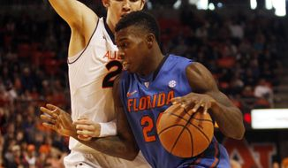 Florida forward Casey Prather (24) drives past Auburn forward Alex Thompson during NCAA college basketball game action in Auburn, Ala., Saturday, Jan. 18, 2014. (AP Photo/Jay Sailors)