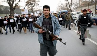 An Afghan police walks ahead of members of civil society organizations for their protection as they march in a street, during an anti terrorism demonstration in Kabul, Afghanistan, Sunday, Jan. 19, 2014. Hundreds of Afghans gathered outside a Lebanese restaurant in Kabul on Sunday to protest against Taliban attack that killed 21 people. The assault Friday by a Taliban bomber and two gunmen against the La Taverna du Liban restaurant was deadliest single attack against foreign civilians in the course of a nearly 13-year U.S.-led war there now approaching its end.  They chanted slogans against terrorism as they laid flowers at the site of the attack. The dead included 13 foreigners and eight Afghans, all civilians. The attack came as security has been deteriorating and apprehension has been growing among Afghans over their country's future as U.S.-led foreign forces prepare for a final withdrawal at the end of the year. (AP Photo/Massoud Hossaini)