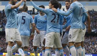 Manchester City's Edin Dzeko, right, celebrates with teammates after scoring against Cardiff City during their English Premier League soccer match at the Etihad Stadium, Manchester, England, Saturday Jan 18, 2014. (AP Photo/Jon Super)