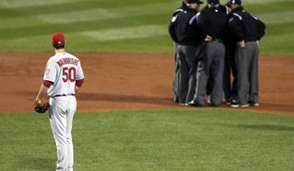 FILE - In this Oct. 23, 2013, file photo, St. Louis Cardinals starting pitcher Adam Wainwright watches as umpires discuss a ruling during the first inning of Game 1 of baseball's World Series against the Boston Red Sox in Boston. Major League Baseball announced Thursday, Jan. 16, 2014, that it will greatly expand instant replay to review close calls starting this season. Each manager will be allowed to challenge at least one call per game. If he's right, he gets another challenge.  After the seventh inning, a crew chief can request a review on his own. (AP Photo/Charles Krupa, File)