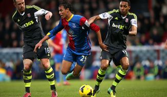 Crystal Palace's Marouane Chamakh, center, takes a tumble under the challenge of Stoke City's Charlie Adam, left, and Steven N'Zonzi, right, during their English Premier League soccer match at Selhurst Park, London, Saturday, Jan. 18, 2014. (AP Photo/John Walton, PA Wire)   UNITED KINGDOM OUT  -  NO SALES  -  NO ARCHIVES