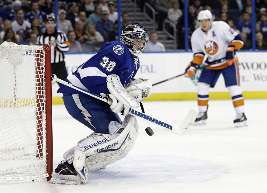 Tampa Bay Lightning goalie Ben Bishop (30) makes a save on a shot as New York Islanders right wing Kyle Okposo (21) closes in during the first period of an NHL hockey game, Thursday, Jan. 16, 2014, in Tampa, Fla. (AP Photo/Chris O'Meara)