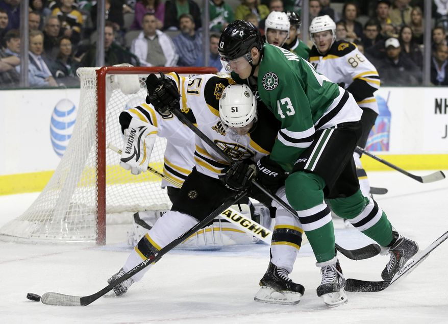 Boston Bruins center Ryan Spooner (51) defends as Dallas Stars' Valeri Nichushkin (43), of Russia, attempts to reach a loose puck during the first period of an NHL hockey game, Thursday, Jan. 16, 2014, in Dallas. (AP Photo/Tony Gutierrez)