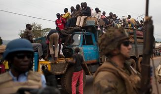FILE - In this Friday, Dec. 27, 2013 file photo, French soldiers protect a truck of fleeing Muslims after it broke down and was surrounded by hundreds of hostile Christian residents, including several anti-balaka militiamen, in the Gobongo neighborhood of Bangui, Central African Republic. Central African Republic has long teetered on the brink of anarchy, but the new unrest unleashed by a March 2013 coup has ignited previously unseen sectarian hatred between Christians and Muslims. More than 1,000 people were killed in December alone and nearly 1 million displaced. The crisis has forced some to flee across borders to desperately poor and unstable countries like Chad and Congo. (AP Photo/Rebecca Blackwell, File)
