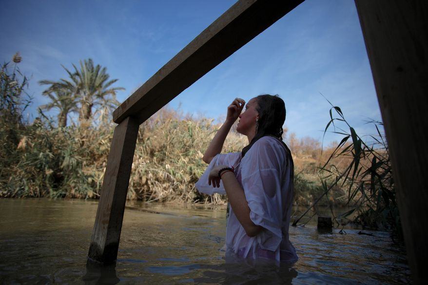 Iryna Zubarenko, 36, from Ukraine, immerses her body into the water of the Jordan River and performs the sign of the cross during a baptism ceremony at the Jordan River baptism site in South Shuna, Jordan Valley, Jordan, Sunday, Jan. 19, 2014. Hundreds of Orthodox Syrian and Iraqi refugee pilgrims, along with foreign and Jordanian Orthodox pilgrims, flock to the annual ceremony for the blessing of the waters at the baptism site where it is believed Jesus Christ was baptized. (AP Photo/Mohammad Hannon)