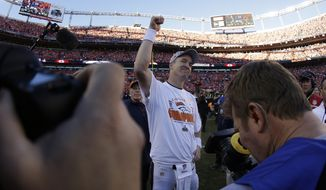 Surrounded by photographers Denver Broncos quarterback Peyton Manning (18) celebrates after the AFC Championship NFL playoff football game in Denver, Sunday, Jan. 19, 2014. The Broncos defeated the Patriots 26-16 to advance to the Super Bowl. (AP Photo/Charlie Riedel)
