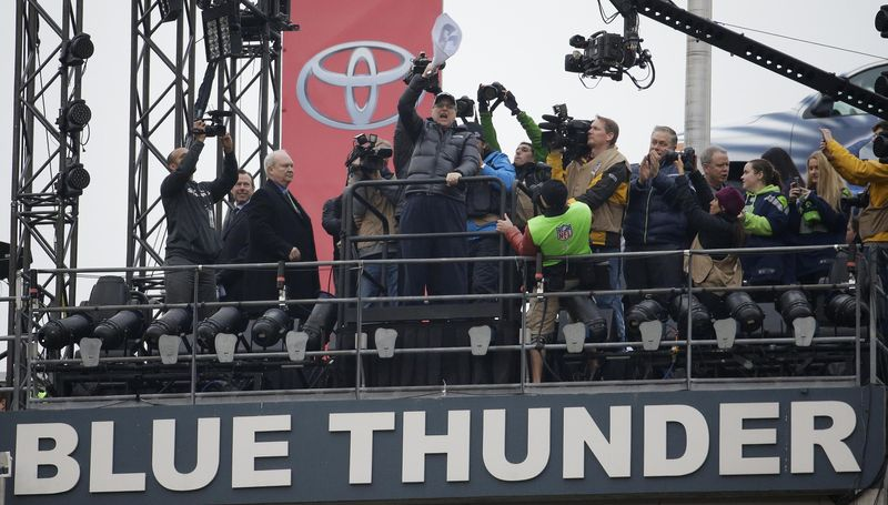 Seattle Seahawks owner Paul Allen raises the 12th man flag before the NFL football NFC Championship game against the San Francisco 49ers, Sunday, Jan. 19, 2014, in Seattle. (AP Photo/Ted S. Warren)