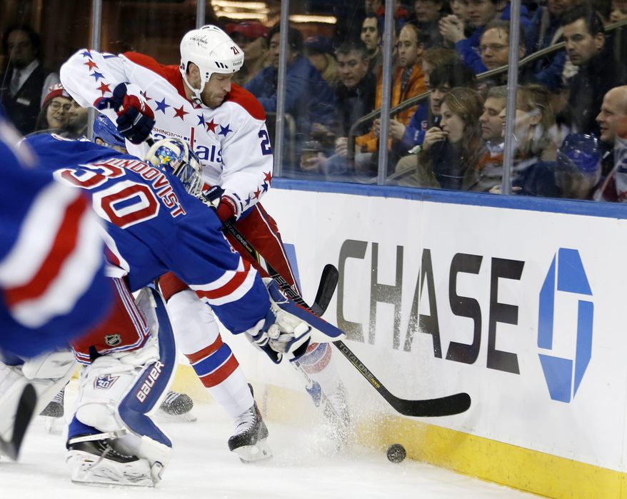 New York Rangers goalie Henrik Lundqvist (30) leaves the crease to defend Washington Capitals center Brooks Laich (21) in the first period of an NHL hockey game at Madison Square Garden in New York, Sunday, Jan. 19, 2014. (AP Photo/Kathy Willens)