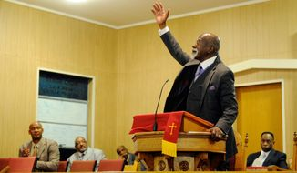 Dr. Anthony Brooks ends his keynote speech celebrating the life and work of Dr. Martin Luther King, Jr. during the Henderson County Black History Committee's program at Greater Norris Chapel Baptist Church in Henderson, Ky Sunday Jan. 19, 2014. (AP Photo/The Gleaner, Darrin Phegley)