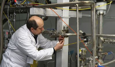 **FILE** An unidentified International Atomic Energy Agency (IAEA) inspector cuts the connections between the twin cascades for 20 percent uranium enrichment at the Natanz facility, some 200 miles (322 kilometers) south of Tehran, on Jan. 20, 2014. (Associated Press/IRNA, Kazem Ghane)