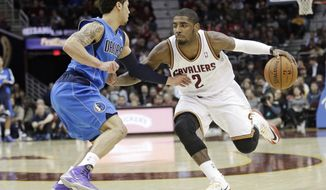 Cleveland Cavaliers' Kyrie Irving (2) drives past Dallas Mavericks' Shane Larkin (3) during the second quarter of an NBA basketball game Monday, Jan. 20, 2014, in Cleveland. (AP Photo/Tony Dejak)