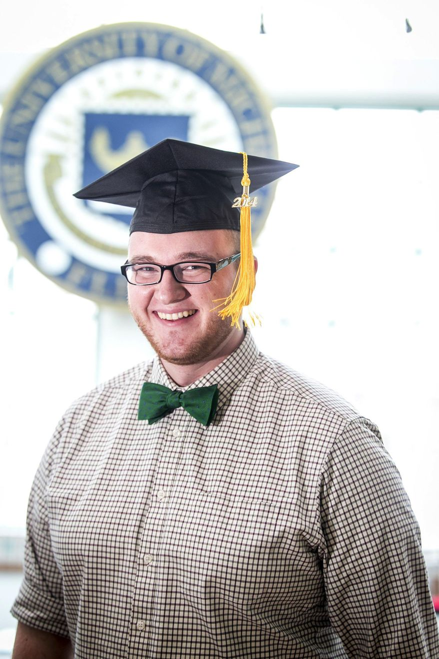 Alex Benda, 22, poses in a gaduation cap at the Michigan Times offices at the University of Michigan-Flint in Flint, Mich. on Friday, Jan. 17, 2014.   Bends says he hopes to sell add space on his graduation cap to take a bite out of his education debt.    (AP Photo/The Detroit Free Press, Jarrad Henderson)  DETROIT NEWS OUT, TV OUT, INTERNET OUT, MAGS OUT, NO SALES, MANDATORY CREDIT DETROIT FREE PRESS
