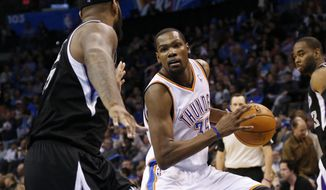 Oklahoma City Thunder forward Kevin Durant (35) drives around Sacramento Kings center DeMarcus Cousins (15) in the third quarter of an NBA basketball game in Oklahoma City, Sunday, Jan. 19, 2014. Oklahoma City won 108-93.(AP Photo/Sue Ogrocki)