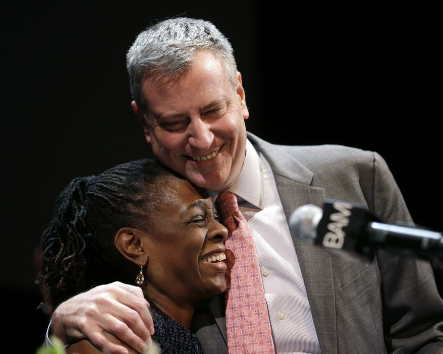 "New York City Mayor Bill de Blasio hugs his wife Chirlane McCray at a tribute to Martin Luther King, Jr. in the Brooklyn borough of New York, Monday, Jan. 20, 2014. De Blasio told a packed audience Monday at the Brooklyn Academy of Music that the ""price of inequality has deepened."" The mayor says economic inequality is closing doors for hard-working people in the city and around the country. (AP Photo/Seth Wenig)"