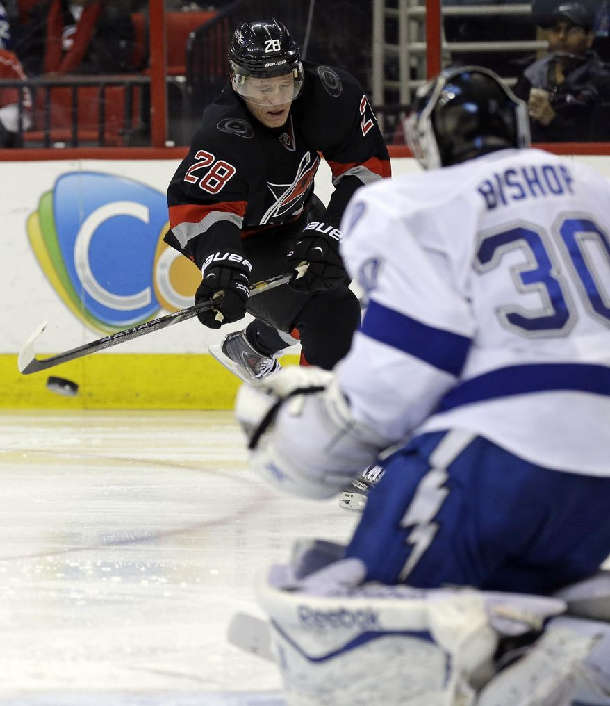 Carolina Hurricanes' Alexander Semin (28), of Russia, shoots and scores on Tampa Bay Lightning goalie Ben Bishop (30) during the second period of an NHL hockey game in Raleigh, N.C., Sunday, Jan. 19, 2014. (AP Photo/Gerry Broome)