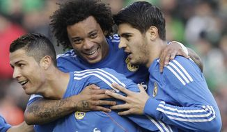 Real Madrid's Cristiano Ronaldo, left, celebrates with teammate Alvaro Morata, right, and Marcelo Vieira, centre, after scoring against Betis during their La Liga soccer match at the Benito Villamarin stadium, in Seville, Spain on Saturday, Jan. 18, 2014. (AP Photo/Angel Fernandez)