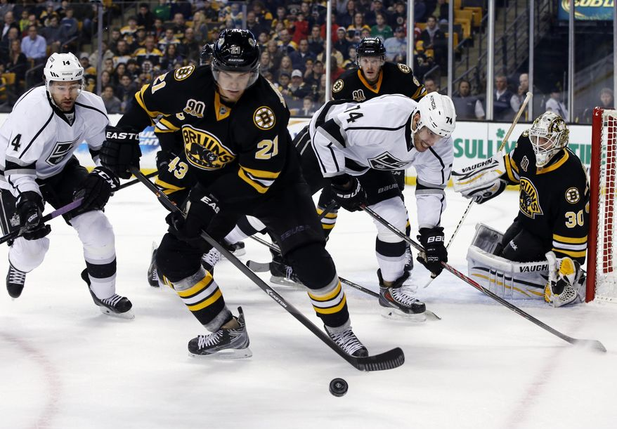 Boston Bruins left wing Loui Eriksson (21) controls the puck against Los Angeles Kings right wing Justin Williams (14) and left wing Dwight King (74) as Bruins goalie Chad Johnson (30) protects the net during the first period of an NHL hockey game in Boston, Monday, Jan. 20, 2014. (AP Photo/Elise Amendola)