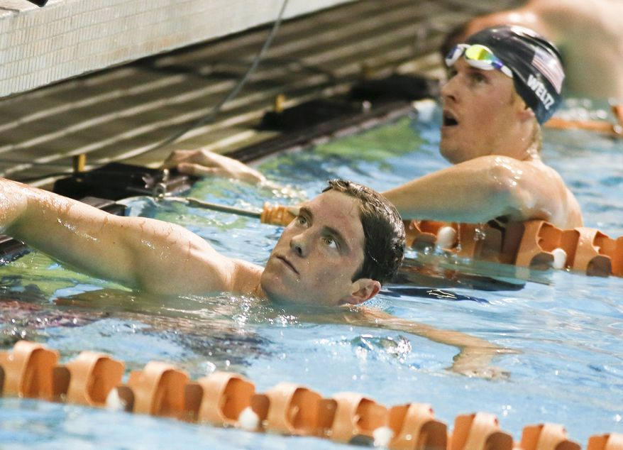 Conor Dwyer, left, looks at his time following the men's 400-meter individual medley final at the Austin Grand Prix, Saturday, Jan. 18, 2014, in Austin, Texas. Dwyer won the event. (AP Photo/Jack Plunkett)