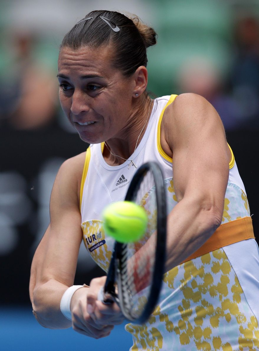 Flavia Pennetta of Italy makes a backhand return to Li Na of China  during their quarterfinal at the Australian Open tennis championship in Melbourne, Australia, Tuesday, Jan. 21, 2014.(AP Photo/Aaron Favila)