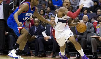 Washington Wizards shooting guard Bradley Beal, right, drives to the basket against Philadelphia 76ers shooting guard Hollis Thompson during the second half of an NBA basketball game on Monday, Jan. 20, 2014 in Washington. The Wizards defeated the 76ers 107-99. (AP Photo/ Evan Vucci)