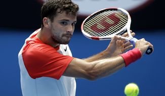 Grigor Dimitrov of Bulgaria hits a backhand return to Roberto Bautista Agut of Spain during their fourth round match at the Australian Open tennis championship in Melbourne, Australia, Monday, Jan. 20, 2014.(AP Photo/Aijaz Rahi)