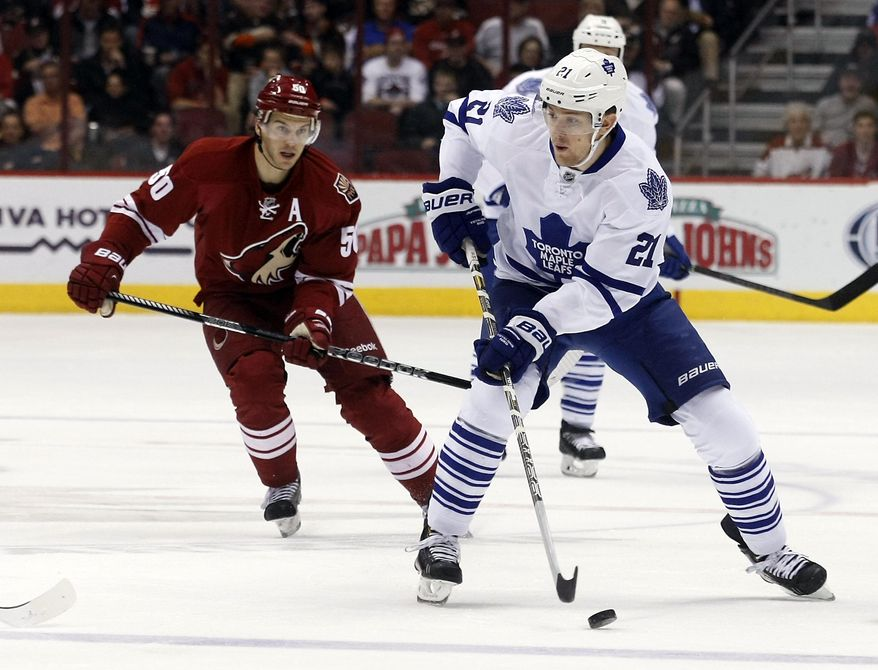 Toronto Maple Leafs left wing James van Riemsdyk (21) carries the puck past Phoenix Coyotes center Antoine Vermette (50) in the first period of an NHL hockey game, Monday, Jan. 20, 2014, in Glendale, Ariz. (AP Photo/Rick Scuteri)