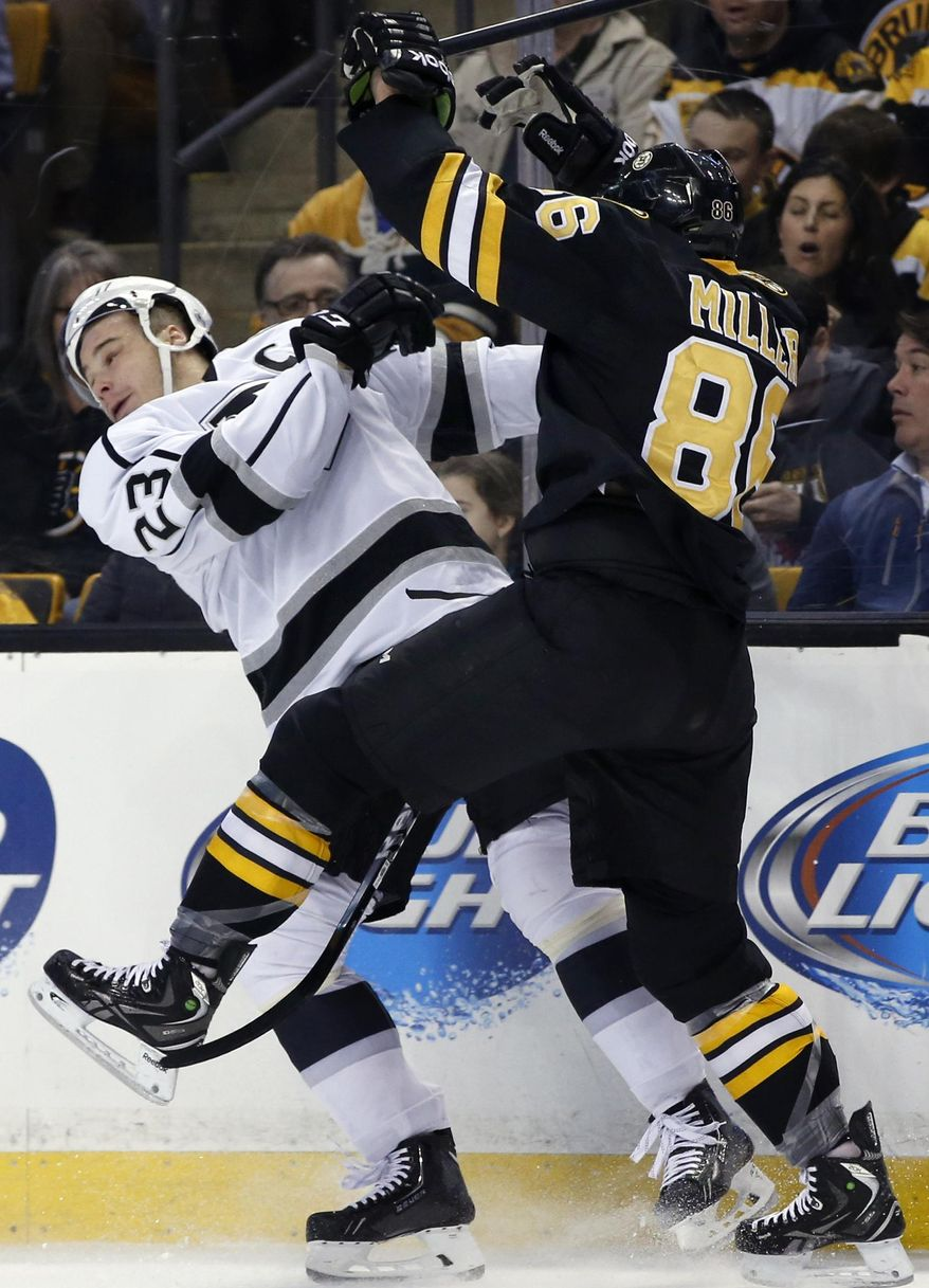 Los Angeles Kings right wing Dustin Brown (23) is checked into the boards by Boston Bruins defenseman Kevan Miller (86) during the first period of an NHL hockey game in Boston Monday, Jan. 20, 2014. (AP Photo/Elise Amendola)