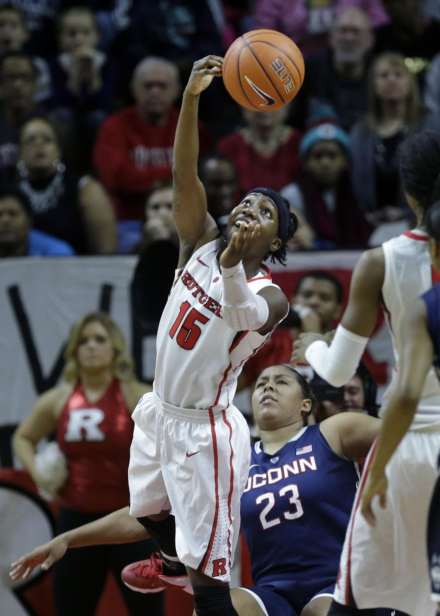 Rutgers guard Syessence Davis (15) takes a shot over her shoulder Connecticut defenders forward Kaleena Mosqueda-Lewis (23) falls during the first half of an NCAA college basketball game Sunday, Jan. 19, 2014, in Piscataway, N.J. (AP Photo/Mel Evans)
