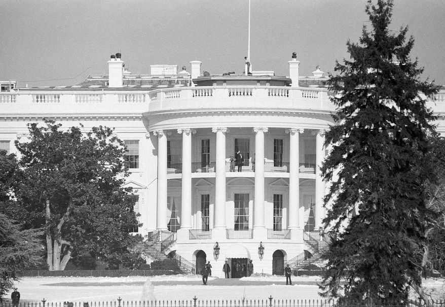 """President Ronald Reagan waves from the Truman Balcony at the White House in Washington to members of the anti-abortion movement that was beginning a """"March for Life"""" demonstration on the Ellipse marking the 11th anniversary of legalized abortion, Jan. 23, 1984. (AP Photo/Ron Edmonds)"""