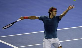 Roger Federer of Switzerland  serves to Jo-Wilfried Tsonga of France during their fourth round match at the Australian Open tennis championship in Melbourne, Australia, Monday, Jan. 20, 2014.(AP Photo/Aijaz Rahi)
