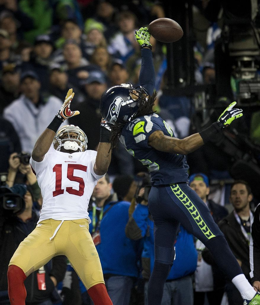 CORRECTS BYLINE TO PAUL KITAGAKI JR.-Seattle Seahawks cornerback Richard Sherman (25) hits the ball away from San Francisco 49ers wide receiver Michael Crabtree (15) and is intercepted by Seattle Seahawks outside linebacker Malcolm Smith (53) during the NFL football NFC Championship game, Sunday, Jan. 19, 2014, in Seattle. The Seahawks won 23-17 to advance to the Super Bowl. (AP Photo/The Sacramento Bee, Paul Kitagaki Jr.) MAGS OUT; TV OUT (KCRA3, KXTV10, KOVR13, KUVS19, KMAZ31, KTXL40) MANDATORY CREDIT