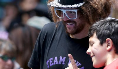 Music artist Redfoo poses for a fan's photo  as he watches his girlfriend Victoria Azarenka of Belarus play Sloane Stephens of the U.S. in their fourth round match at the Australian Open tennis championship in Melbourne, Australia, Monday, Jan. 20, 2014. (AP Photo/Aaron Favila)