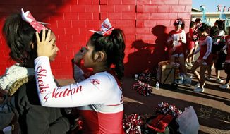 Michelle Oliveros, second from left, applies makeup to Blair Robinson both part of the Hollywood High School marching in preparation for the Martin Luther King Jr. parade in Los Angeles on Monday Jan. 20, 2014. The 29th annual Kingdom Day Parade honoring Martin Luther King Jr. was themed  ``Ain't Gonna Let Nobody Turn Us Round.'' (AP Photo/Richard Vogel)