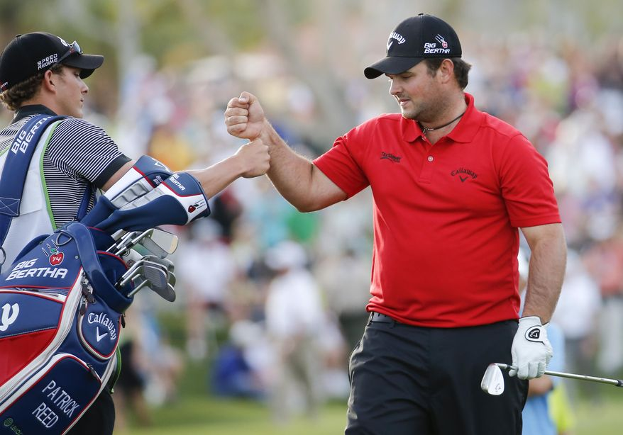 Patrick Reed, right, celebrates with his caddie Kessler Karain after winning the Humana Challenge golf tournament on the Palmer Private course at PGA West, Sunday, Jan. 19, 2014 in La Quinta, Calif. (AP Photo/Matt York)