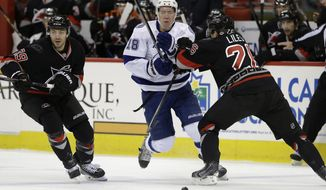 Tampa Bay Lightning's Ondrej Palat (18), of the Czech Republic, chases the puck as Carolina Hurricanes' John-Michael Liles and Patrick Dwyer (39) block during the first period of an NHL hockey game in Raleigh, N.C., Sunday, Jan. 19, 2014. (AP Photo/Gerry Broome)