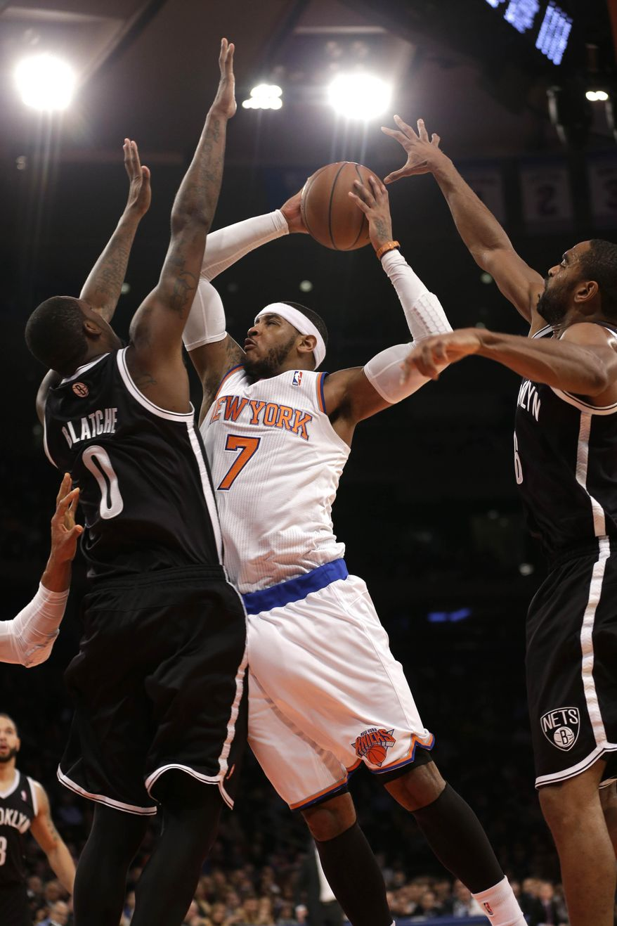 New York Knicks' Carmelo Anthony, center, is fouled by Brooklyn Nets' Andray Blatche, left, while driving to the basket past Blatche and Alan Anderson during the first half of the NBA basketball game at Madison Square Garden, Monday, Jan. 20, 2014, in New York. (AP Photo/Seth Wenig)
