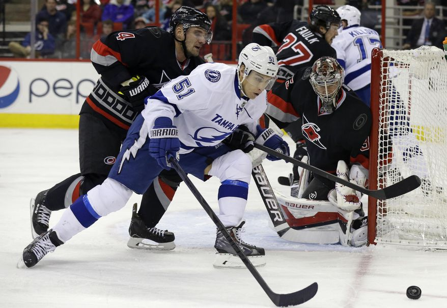 Tampa Bay Lightning's Valtteri Filppula (51), of Finland, tries to shoot as Carolina Hurricanes' Andrej Sekera (4), of Slovakia, and goalie Justin Peters defend during the first period of an NHL hockey game in Raleigh, N.C., Sunday, Jan. 19, 2014. (AP Photo/Gerry Broome)