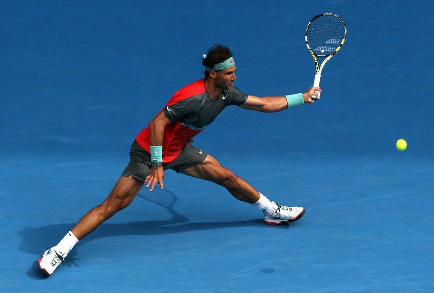 Rafael Nadal of Spain makes a forehand return to Kei Nishikori of Japan during their fourth round match at the Australian Open tennis championship in Melbourne, Australia, Monday, Jan. 20, 2014.(AP Photo/Eugene Hoshiko)