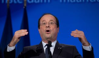 French President Francois Hollande raises his hands during a speech at the National Maritime Museum in Amsterdam, Netherlands, Monday, Jan. 20, 2014. (AP Photo/Peter Dejong)